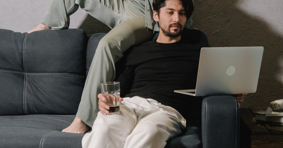A man sitting on a couch with a laptop